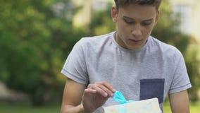 Tiener die huidig, wachtend op meisje, zenuwachtig over eerste datum houden stock footage