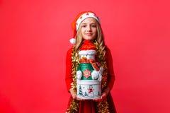 Tiener die Kerstmanhoed en klatergoud op de dozen van de Kerstmisgift van de halsholding, op rode achtergrond dragen Het concept  royalty-vrije stock afbeeldingen