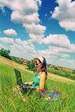 Tiener die laptop op gebied met behulp van Stock Foto's