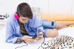 Tiener die met mobiele telefoon aan muziek luisteren stock foto