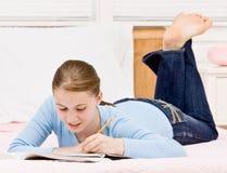 Tiener die in notitieboekje op bed schrijft Royalty-vrije Stock Foto