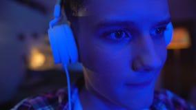 Tiener die oortelefoons en het spelen videospelletje aanzetten, cybersports vrije tijd stock video