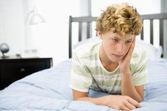 Tiener die op Bed ligt Stock Afbeelding