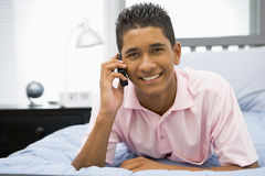 Tiener die op Bed ligt dat Mobiele Telefoon met behulp van Royalty-vrije Stock Foto's