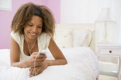 Tiener die op Bed ligt dat Mp3 Speler met behulp van Royalty-vrije Stock Afbeeldingen