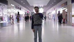 Tiener die op de telefoon in een winkelcentrum spreken stock video