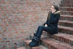 Tiener die op smartphone buiten spreken stock afbeeldingen
