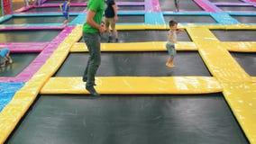 Tiener die op trampoline, kinderen springen die pret op trampoline hebben bij lokaal pretpark, sport stock footage