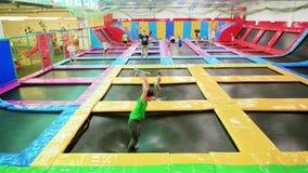 Tiener die op trampoline springen, die acrobatische trucs op trampolines in lokaal pretpark maken stock video
