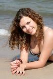 Tiener die op zand ligt Stock Fotografie