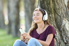 Tiener die in openlucht online muziek voelen stock foto's