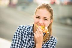 Tiener die pizza in straat eten stock fotografie