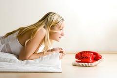 Tiener die rode telefoon bekijkt royalty-vrije stock afbeelding