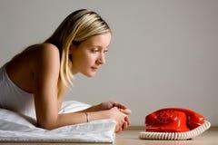 Tiener die rode telefoon bekijkt Royalty-vrije Stock Afbeeldingen