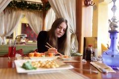 Tiener die sushi eet Stock Afbeeldingen