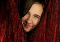 Tiener die van achter rode gordijnen gluurt stock fotografie