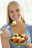 Tiener die Verse Fruitsalade eet Stock Afbeelding