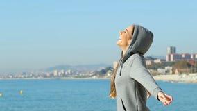 Tiener die verse lucht op het strand ademen