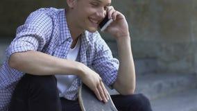 Tiener die vrienden op smartphone roepen, die skateboard, hobby gaan berijden stock videobeelden