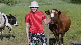 Tiener die in weiland zich dichtbij met koeien bevinden en glas verse melk houden Gezonde Levensstijl stock video