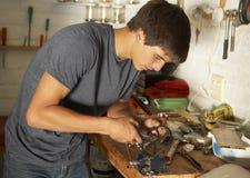 Tiener die Werkbank in Garage gebruiken stock afbeeldingen