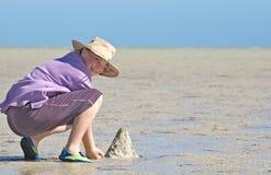 Tiener die zandkastelen maakt Stock Foto's