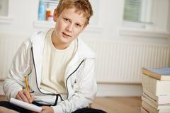 Tiener die zijn thuiswerk doet Stock Foto