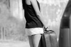 Tiener donkerbruine vrouw die een grote leerkoffer houden stock fotografie