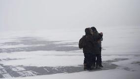 Tiener drie maakt een portret in het ijs van rivier in de winter stock video