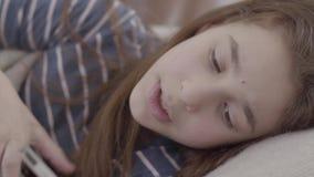 Tiener in een deken wordt verpakt die in bed liggen die temperatuur dicht controleren op thermometer die Het meisje voelt slecht, stock video