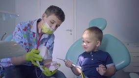 Tiener en zijn kleine broer die in tandartsbureau spelen Oudere broer die de jongen onderwijzen om tanden gebruiken te borstelen stock videobeelden