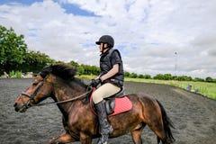 Tiener gezien genietend van bij de galop met een poney stock fotografie