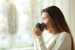 Tiener het drinken koffie die door een venster kijken een regenachtige dag stock afbeeldingen