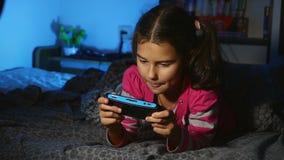 Tiener het spelen meisjes draagbaar videospelletje een consolejong geitje bij nacht binnen stock videobeelden