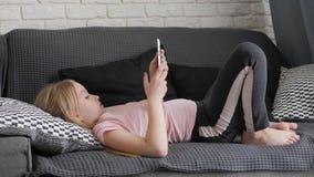 Tiener het spelen op tabletpc die op een bank thuis rusten Mensen, technologie en vrije tijdsconcept stock video