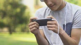 Tiener het spelen videospelletje op telefoon, zenuwachtig en geïrriteerd, gokkenwanorde stock footage