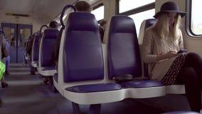 Tiener hipster meisje het luisteren muziek en het typen bericht op telefoon in elektrische trein stock videobeelden