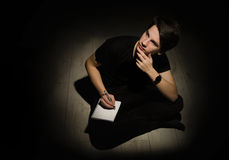 Tiener jonge mens die en op notitieboekje op zwarte bac denken schrijven Royalty-vrije Stock Foto's
