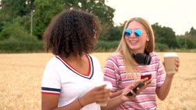 Tiener jonge vrouwen die zonnebril dragen die koffie drinken en selfies op hun smartphones nemen stock videobeelden