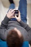 Tiener kerel die sms aan zijn vrienden schrijft Royalty-vrije Stock Foto