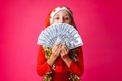 Tiener, in Kerstman` s hoed en met klatergoud op haar hals, met D royalty-vrije stock afbeelding