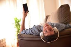 Tiener liggend gezicht die - omhoog op laag doen leunen die aan muziek luisteren Stock Fotografie