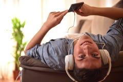 Tiener liggend gezicht die - omhoog op laag het luisteren muziekclose-up doen leunen Stock Foto's