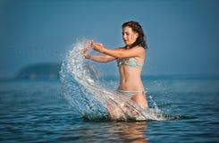 tiener meisje het spelen met golven bij het strand. Royalty-vrije Stock Foto