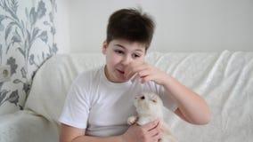 Tiener met een allergie voor katten die neus krassen stock videobeelden