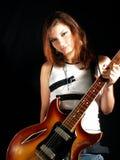 Tiener met een atitude die een elektrische gitaar houdt Stock Afbeeldingen