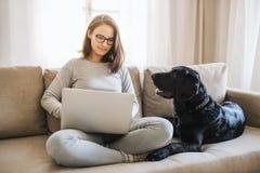 Tiener met een hondzitting op een bank die binnen, aan laptop werken royalty-vrije stock foto