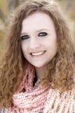 Tiener met krullend bruin haar die perzik gekleurde kap dragen Stock Afbeelding