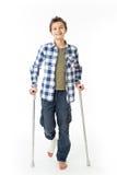 Tiener met steunpilaren en een verband op zijn juist been Stock Afbeelding