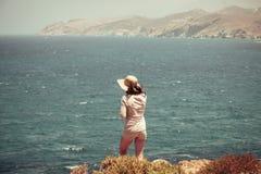 Tiener met strohoed die zich op een klip bevinden Stock Fotografie